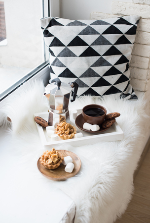 Cozy winter home arrangement on windowsill, coffee and cookies o Stock Photo