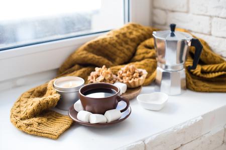 Warm home arrangement on windowsill, coffee and cookies with can Фото со стока