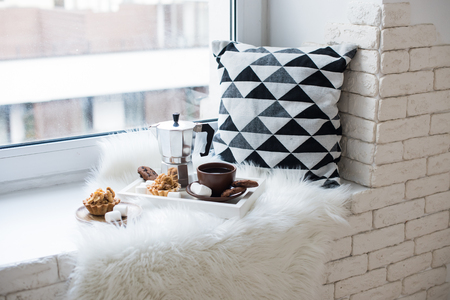 Cozy winter home arrangement on windowsill, coffee and cookies o Foto de archivo