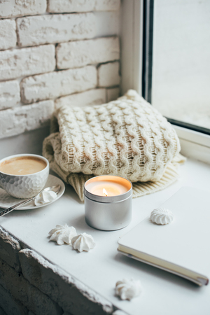 Cozy winter home interior with knitted blanket and candle Фото со стока