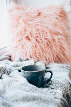 Cup of coffee, knitted blanket and fluffy pillow on cozy windowsill