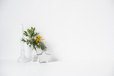 Small bouquet with green leaves and mimosa flowers and empty white wall 写真素材