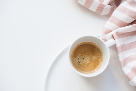 Fresh coffee and cloth with beige stripes on white background