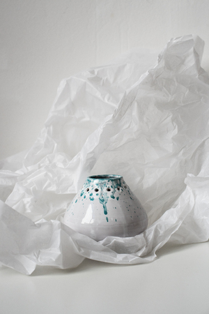 Handmade ceramic vase on dented white paper 写真素材