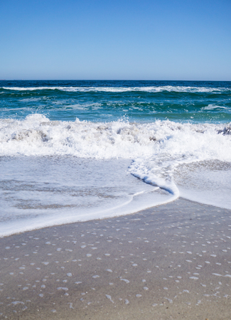 Sea waves on the beach, bright blue water