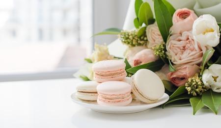 Macarons dulces elegantes y flores beige de color pastel