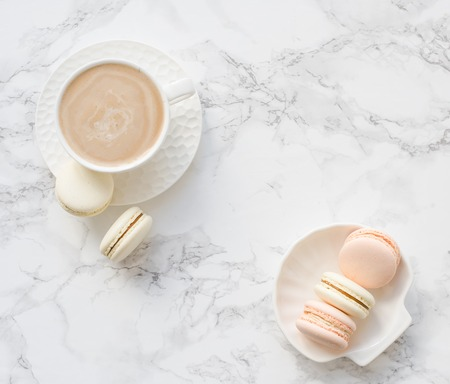 Elegant sweet dessert macarons and cup of coffee on white marble table