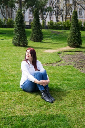 Young woman in white shirt and blue jeans sitting on a green grass