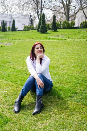 Young woman in white shirt and blue jeans sitting on a green grass Фото со стока - 122661596