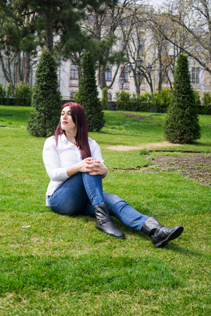 Young woman in white shirt and blue jeans sitting on a green grass Фото со стока - 122661598