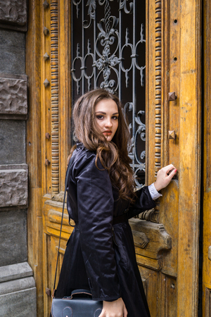 Beautiful young lady in black coat posing