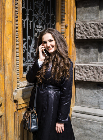 Young lady in black coat with long beautiful hair speaking on a phone
