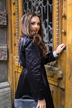 Beautiful young lady in black coat posing
