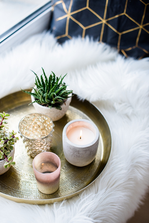 Cozy real home decoration, burning candles on golden tray with pillow on white faux fur on windowsill