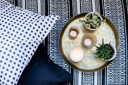 Real apartment interior decor, aromatic candles and plants on vintage tray with pillows and carpet on the floor