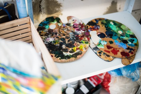 Palette of mixed paints in artists studio, painters workshop details close-up