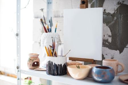 Matite, tela e pennelli sullo scaffale in studio artistico, primo piano dell'attrezzatura del pittore