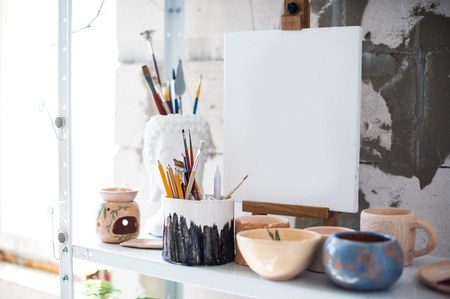 Pencils, canvas and brushes on shelf in artistic studio, painters equipment close-up 写真素材