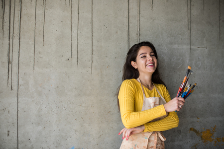 Young beautiful lady artist in apron with paint stains in her loft artistic studio Stock Photo - 122584736