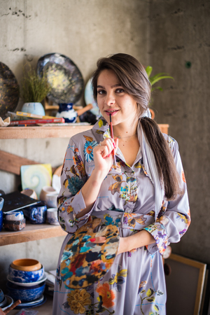 Beautiful lady artist standing in her studio, creative business owner Foto de archivo