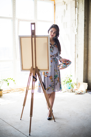 Young beautiful lady painter in dress, woman artist painting