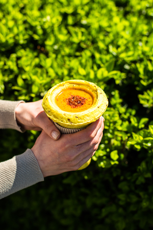 Woman holding healthy vegan street food in her hands, fresh hot vegetable soup in cup Stockfoto