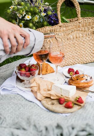 Mans hand pouring rose wine into glasses, summer picnic