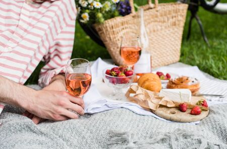 Mans hand holding glass of rose wine, summer picnic with cheese and wine
