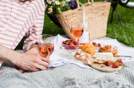 Mans ręka trzyma kieliszek wina różowego, letni piknik z serem i winem