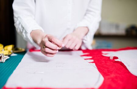 Hands of lady tailor working in her studio, tools and fabric samples on the sewing table Stock Photo