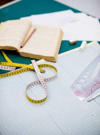 Tools, patterns and fabric samples on the sewing table in the tailor workshop