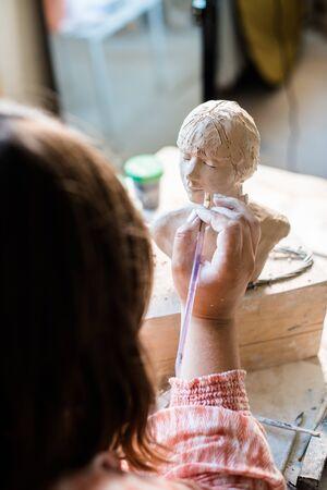 Lady sculptor working in her studio, ceramis artists hands