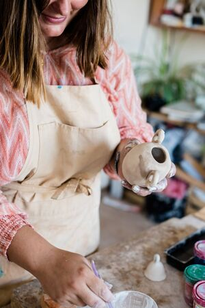 Lady ceramic artist working in her studio interior, woman's hands painting objects out of natural clay