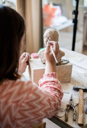 Lady sculptor working in her studio, ceramis artist's hands making objects out of natural clay