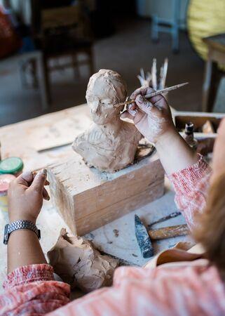 Dame-beeldhouwer aan het werk in haar atelier, handen van keramiekkunstenaars die objecten maken van natuurlijke klei natural