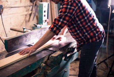 Jonge knappe schrijnwerker die met hout werkt in zijn timmerwerkplaats Stockfoto