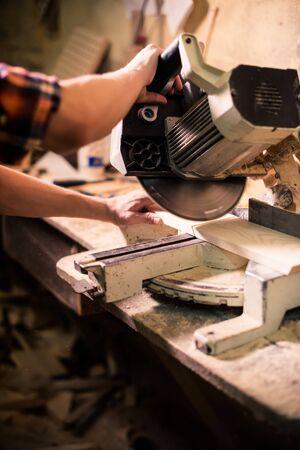 Junger hübscher Tischler, der in seiner Tischlerei mit Holz arbeitet wood Standard-Bild
