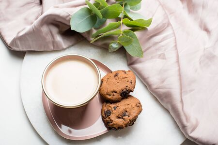 Beautiful enameled cup of coffee with cookies and silk cloth Stock Photo