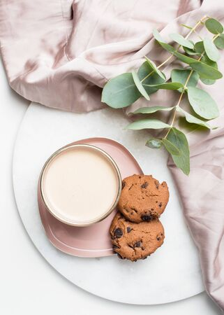Beautiful enameled cup of coffee with cookies and silk cloth Stockfoto