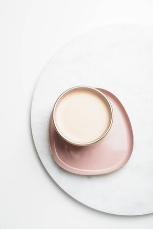 Beautiful enameled pink cup of coffee on white table