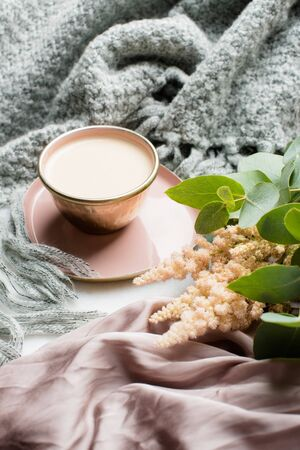Beautiful enameled cup of coffee with pink silk and knitted blanket Stockfoto