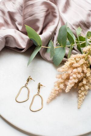 Golden earrings on jewelry plate with beige silk cloth