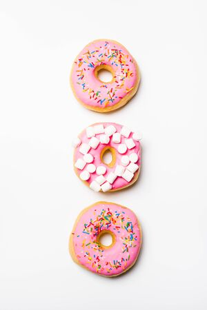 Fresh sweet pink bonuts on white studio background