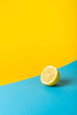 Natural fresh juicy lemons on yellow and blue background