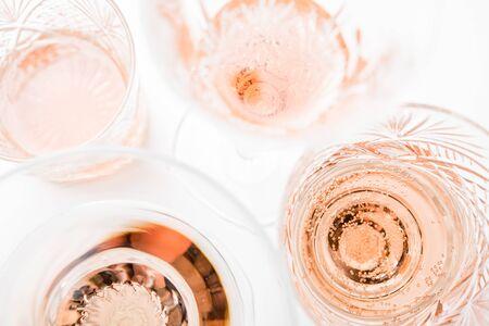 Vino rosado espumoso en diferentes vasos sobre fondo blanco.