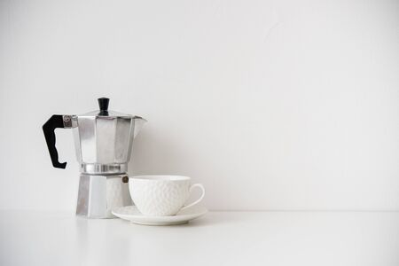 Metal coffee maker and white porcelain cup on table with blank wall