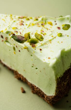 One slice of pistachio cheesecake on sight green background
