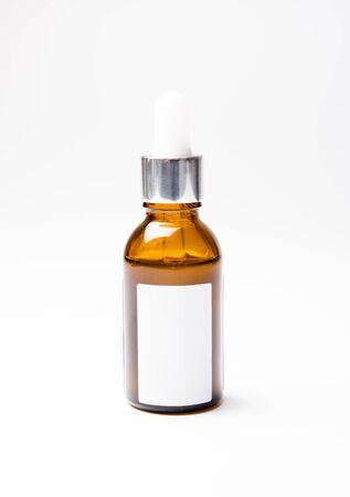 Maqueta de botella cosmética de vidrio marrón con etiqueta blanca en blanco, envasado de suero con pipeta foto de estudio