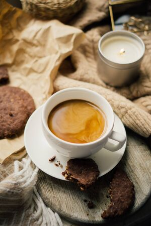 Cup of coffee with milk and chocolate cookies on warm wool blanket