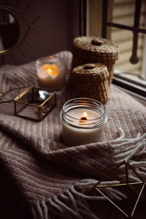 Burning hand-made candle with wooden wick in glass jar